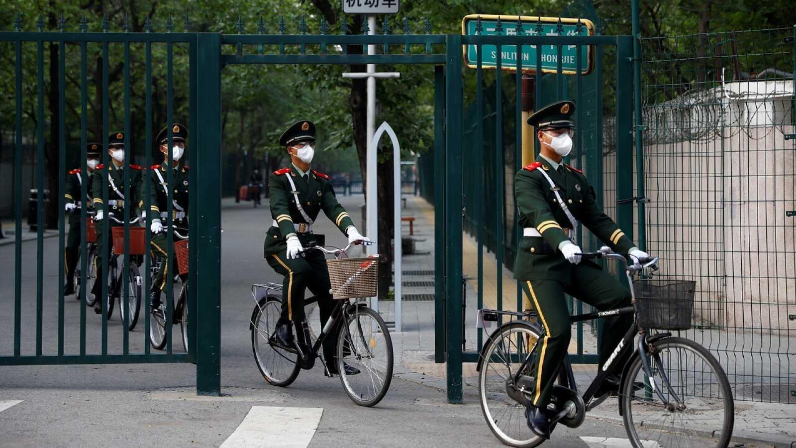 Oficiales paramilitares montan en bicicleta en Pekín