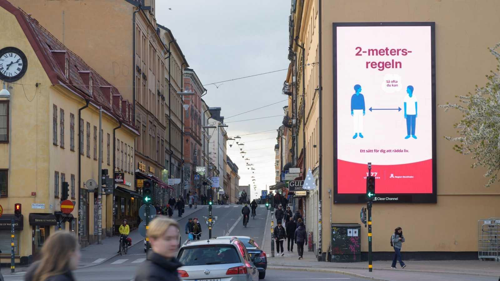 Cartel publicitario en Estocolmo recordando mantener la distancia entre personas