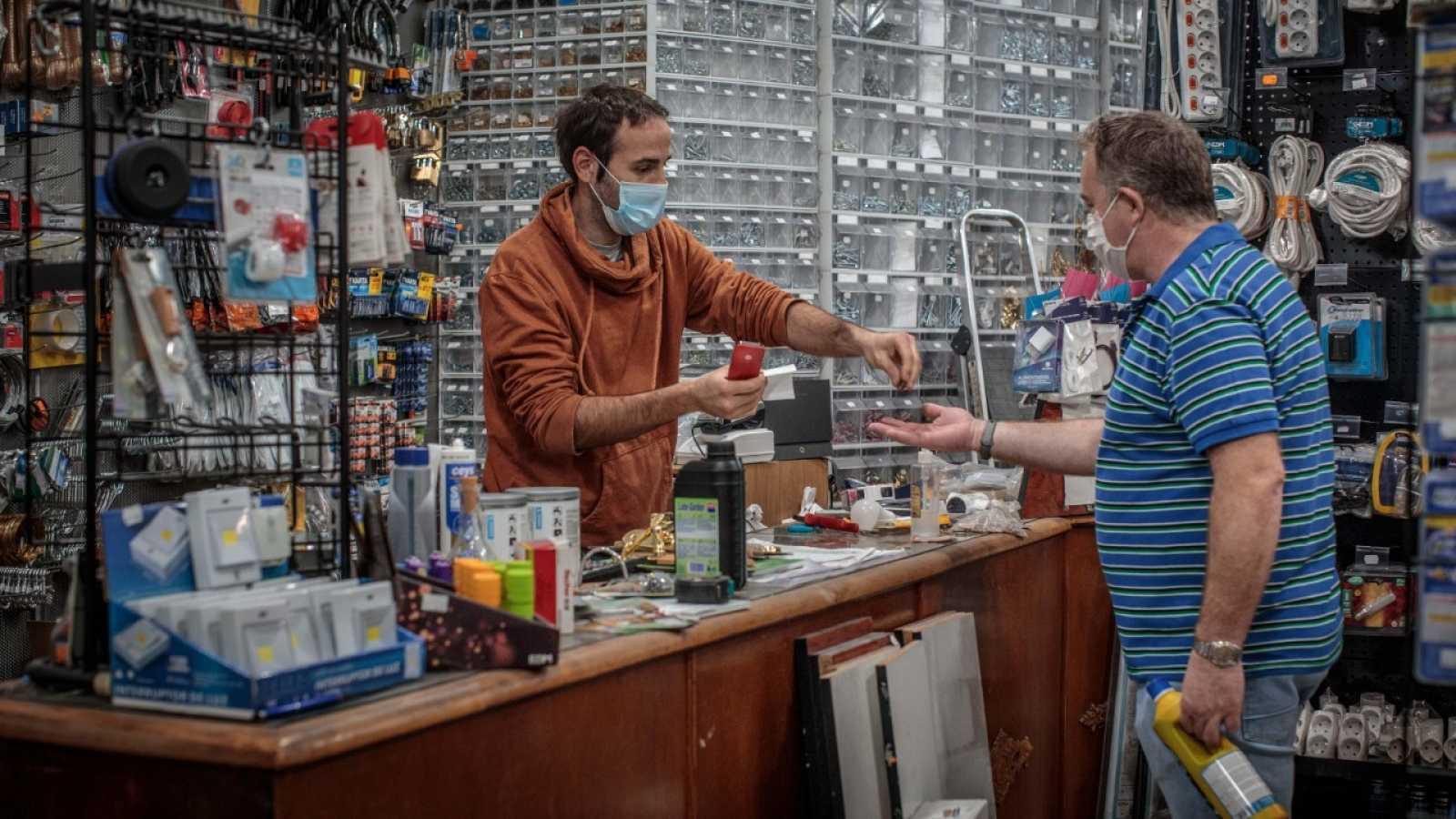 El responsable de una ferretería atiende a sus primeros clientes durante el primer día de la fase 0 de la desescalada.