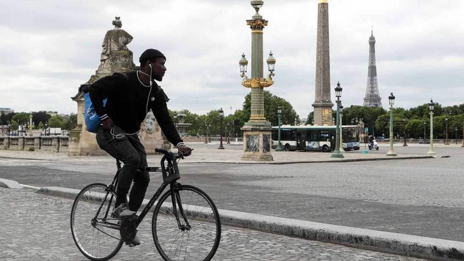 un ciclista con una mochila típica de reparto a domicilio, por el centro de París