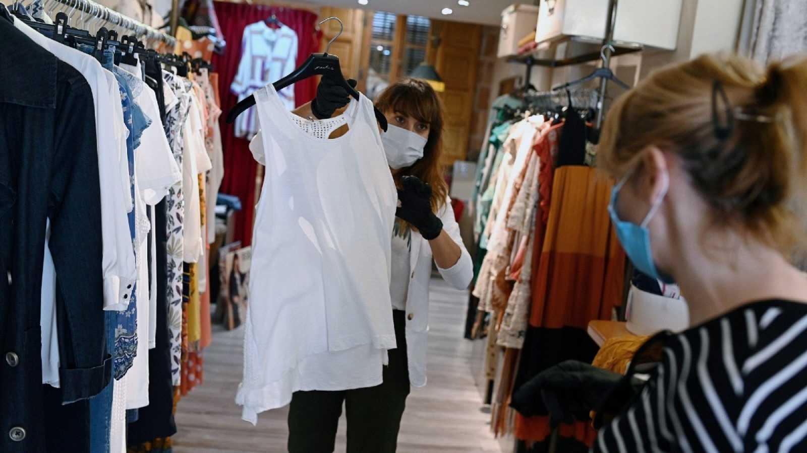 Una trabajadora muestra ropa a una clienta en un comercio