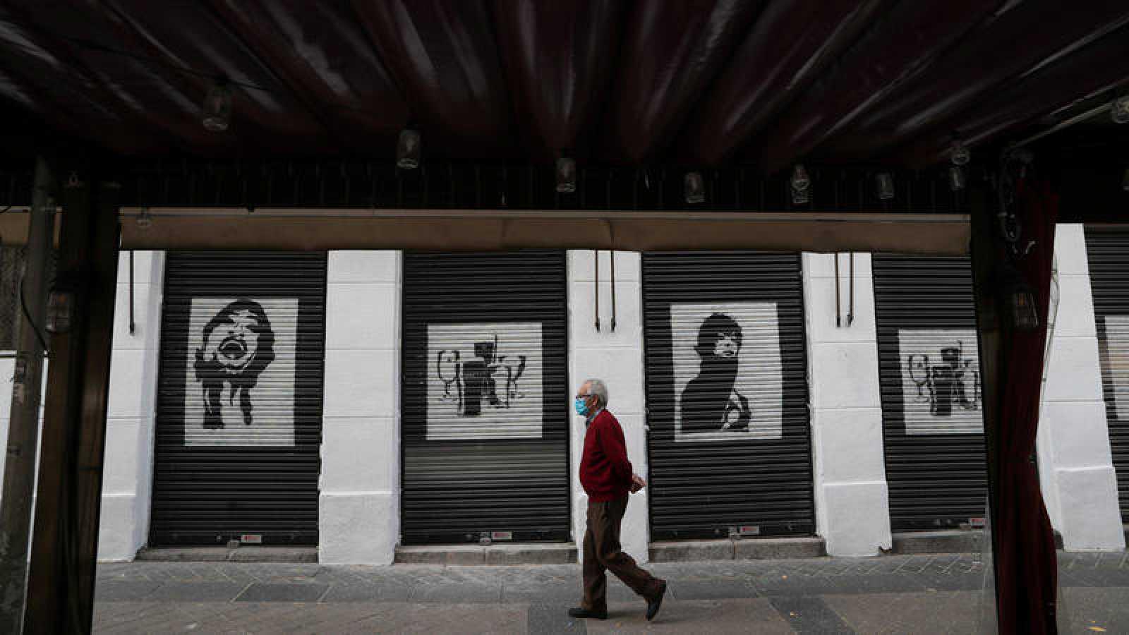 Un anciano pasa por delante de un restaurante cerrado