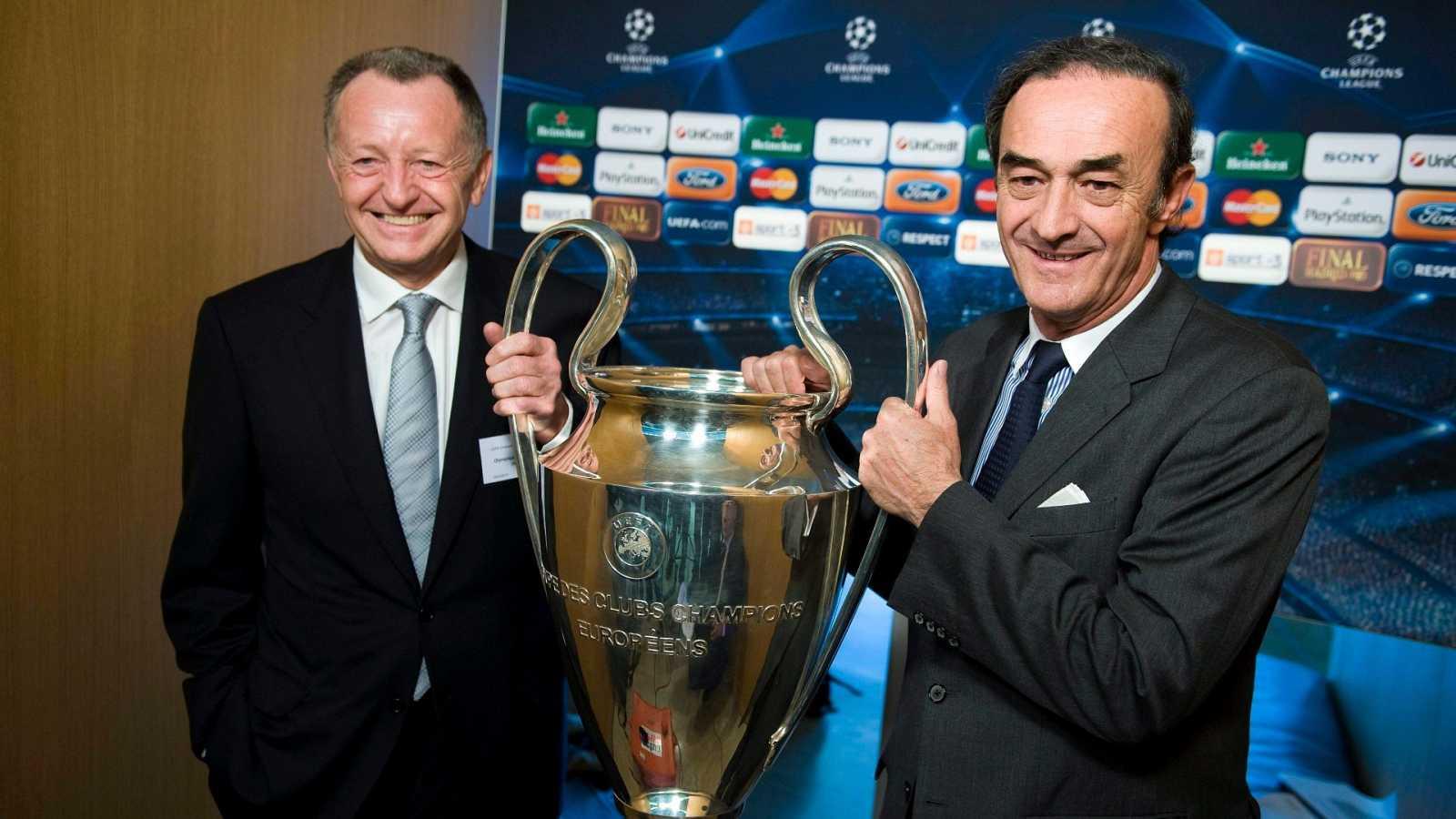 Jean Michel Aulas (i), presidente del Olympique de Lyon, sostiene el trofeo de la Champions League