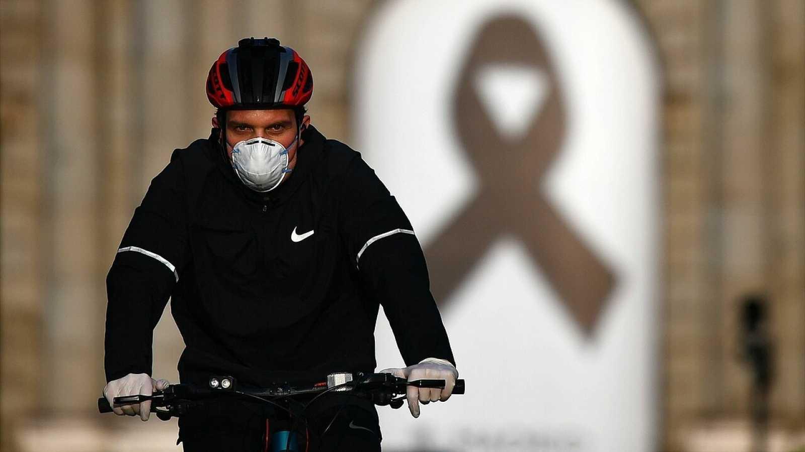 Un ciclista pasa frente a la Puerta de Alcalá, en Madrid, donde se ha colocado un lazo negro como homenaje a las víctimas del coronavirus. Foto: Gabriel BOUYS / AFP.