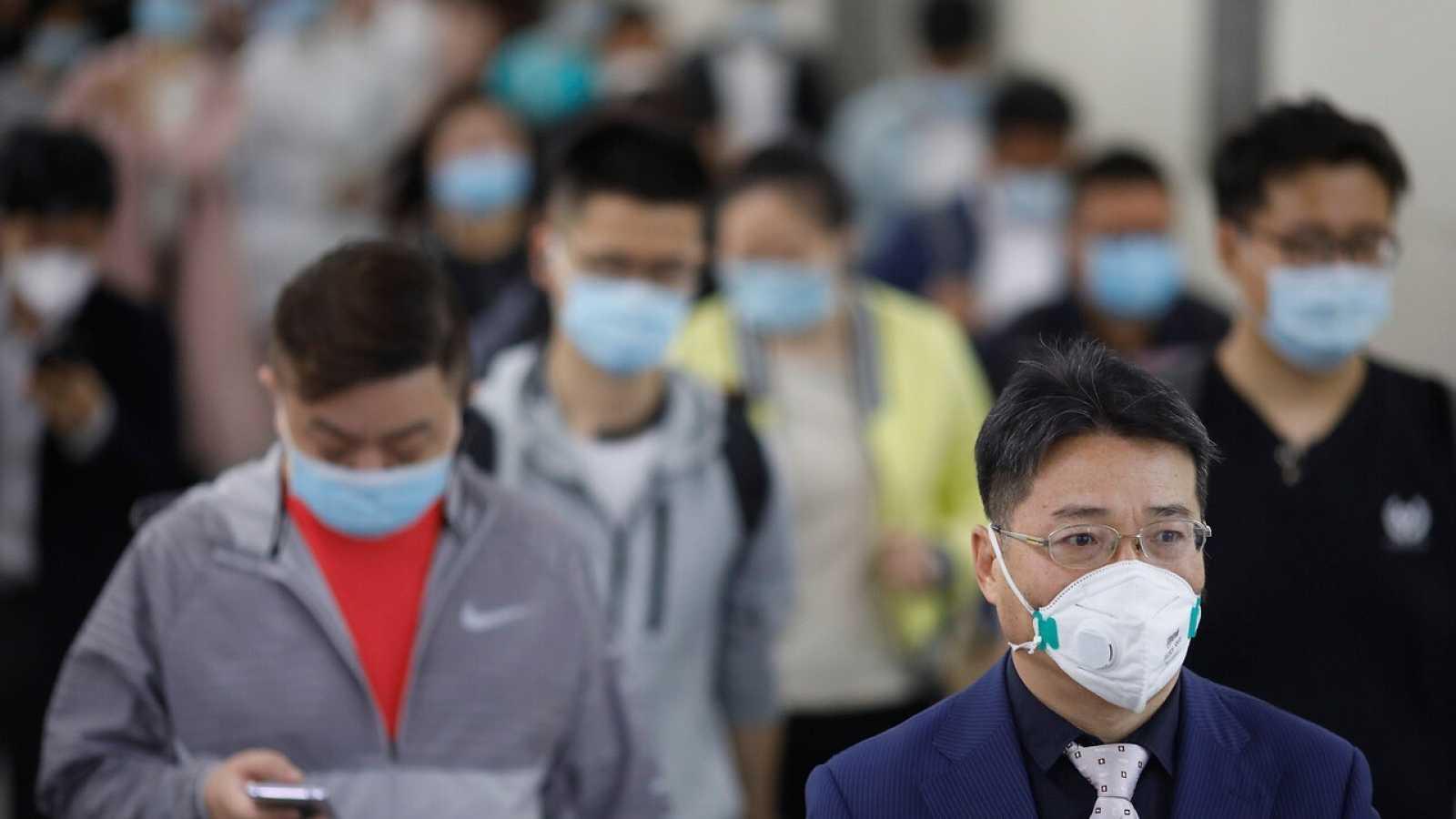 Una multitud de personas con mascarillas en el metro de Pekín