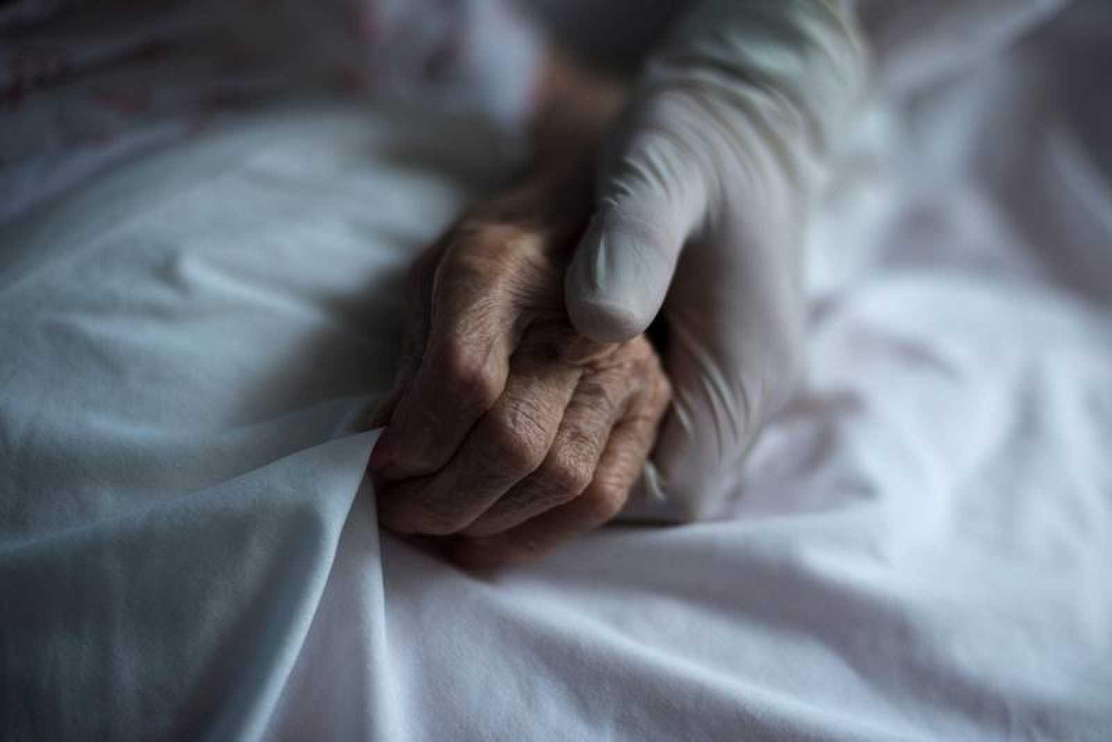 Una trabajadora equipada con guantes sujeta la mano de una residente en un geriátrico