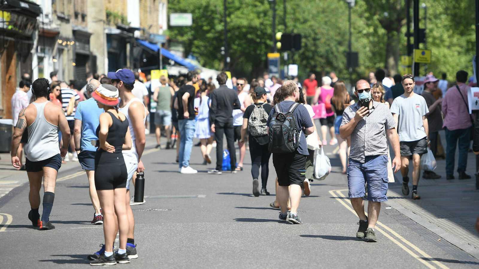 Ciudadanos caminan en el mercado de Broadway en el este de Londres, en Reino Unido, el primer día de alivio de las medidas de co