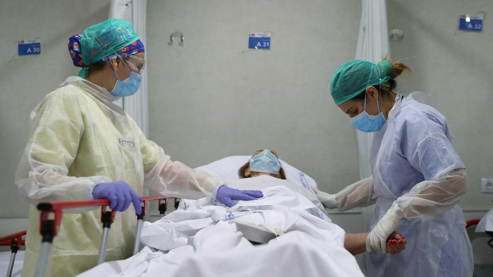 Dos profesionales sanitarios atienden a una persona enferma de coronavirus en el Hospital Infanta Sofía de Madrid