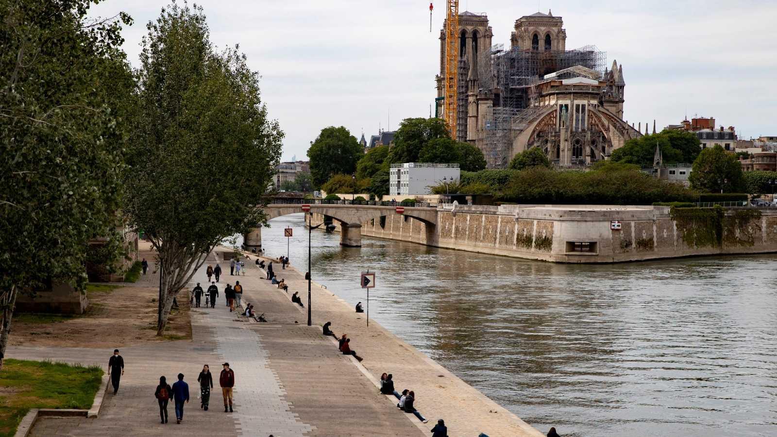 Varias personas pasean cerca del río Sena a su paso por la catedral de Notre Dame