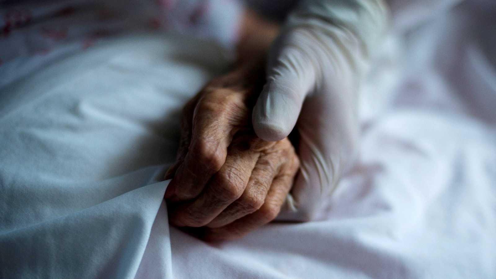 Imagen de una trabajadora sujetando la mano de una residente