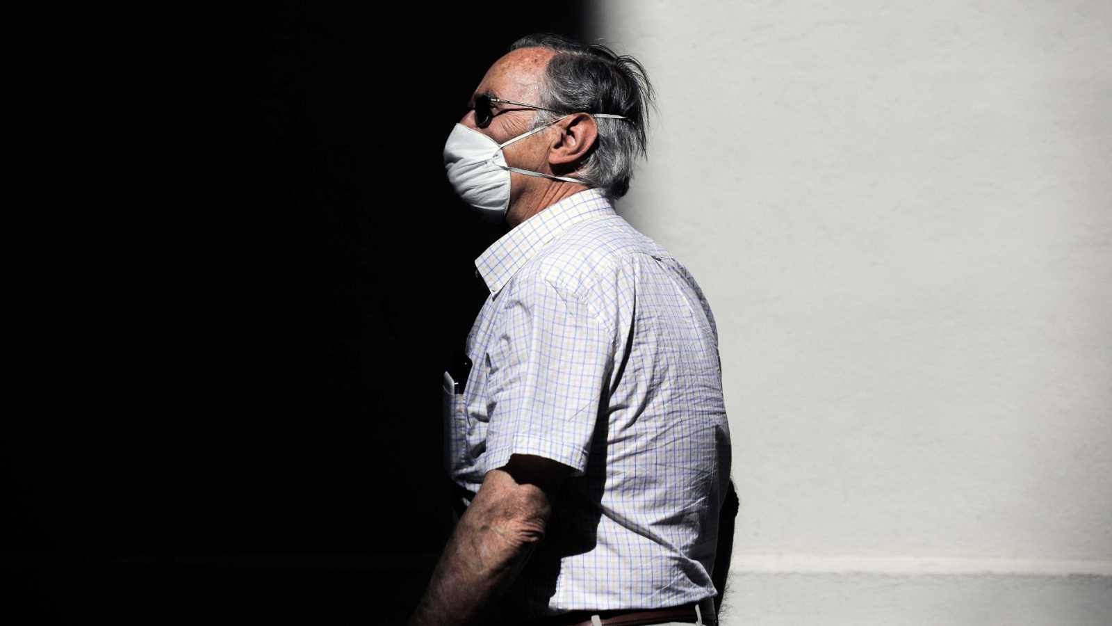 Una persona protegida con mascarilla recorre una calle en Valencia