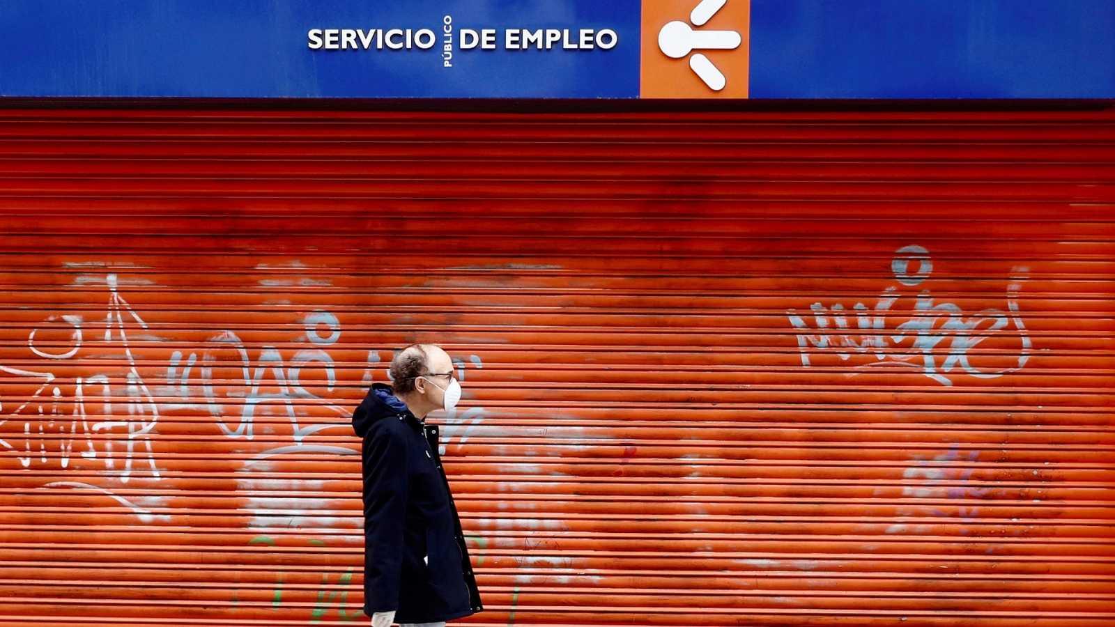 Un hombre con mascarilla camina en frente a una oficina de empleo cerrada en Oviedo.