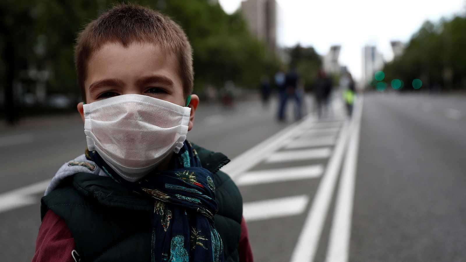 Un niño posa con una mascarilla en el Paseo de la Castellana, en Madrid.