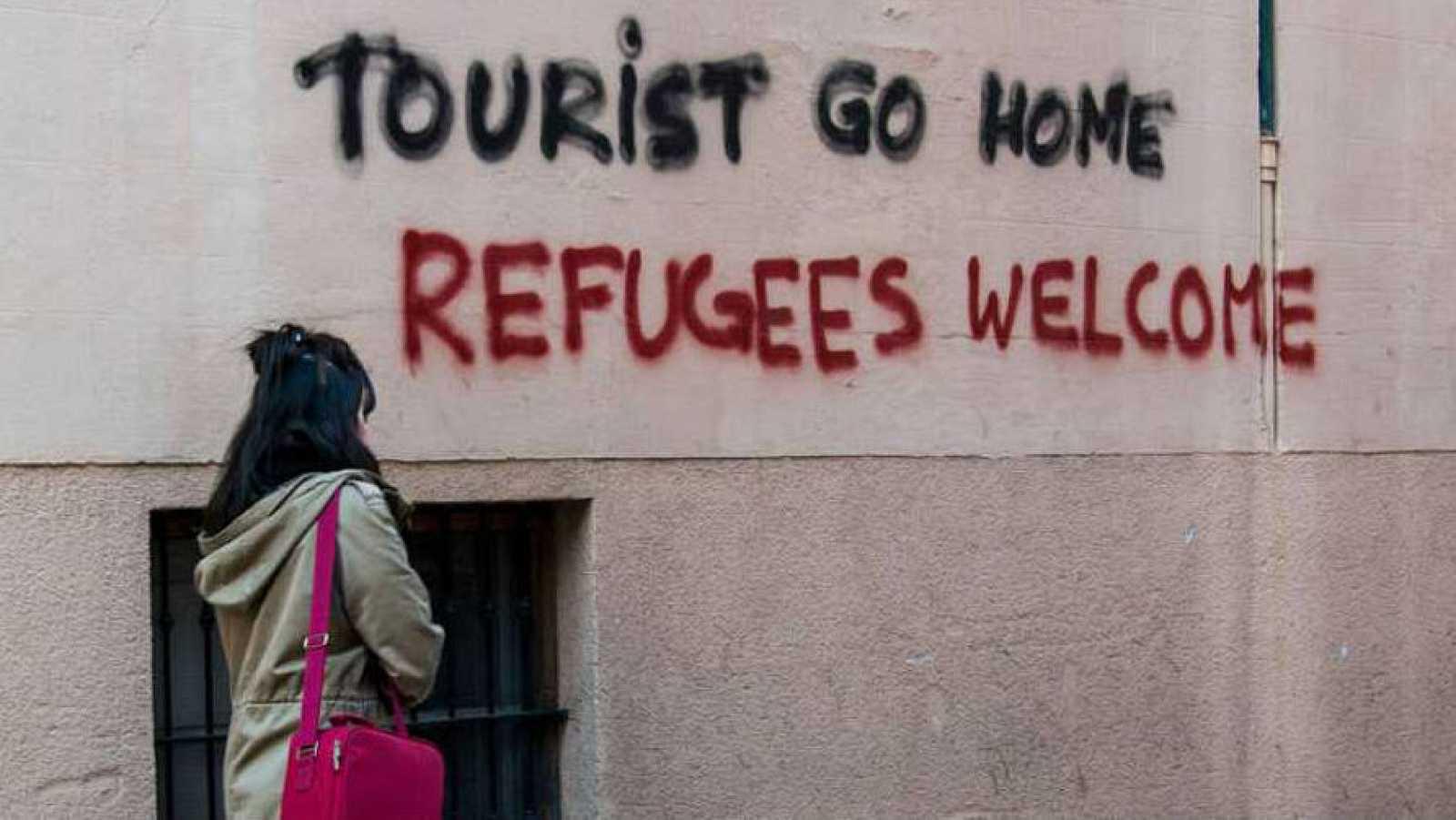 """Imagen de archivo con una pintada en la que se puede leer """"fuera turista"""" y """"bienvenidos refugiados""""."""