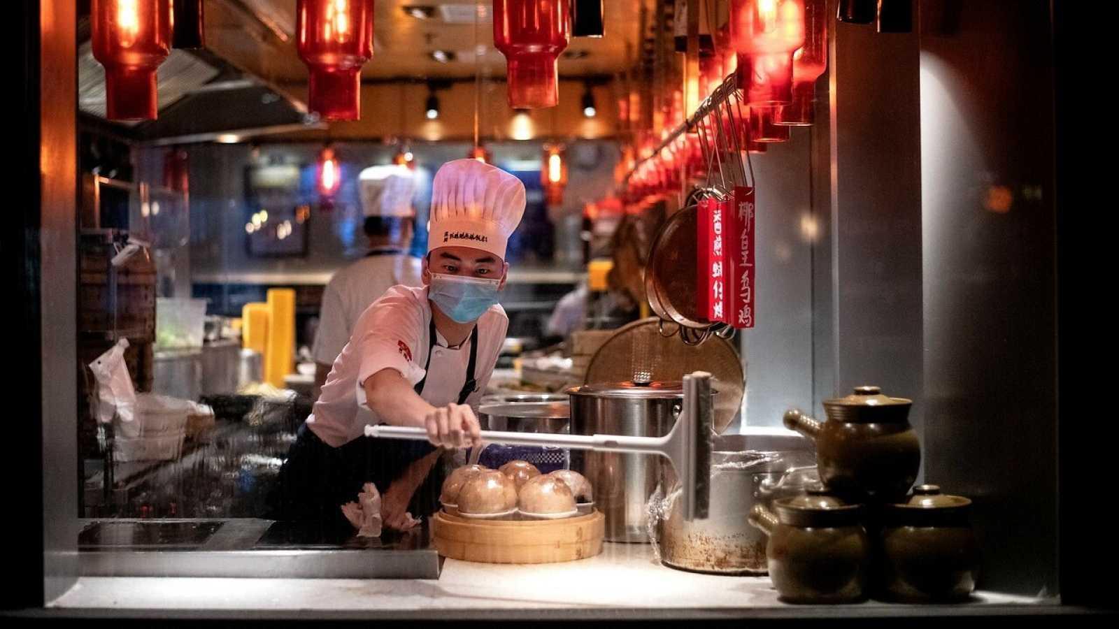 Un empleado limpia la ventana del restaurante en Shenzhen, China