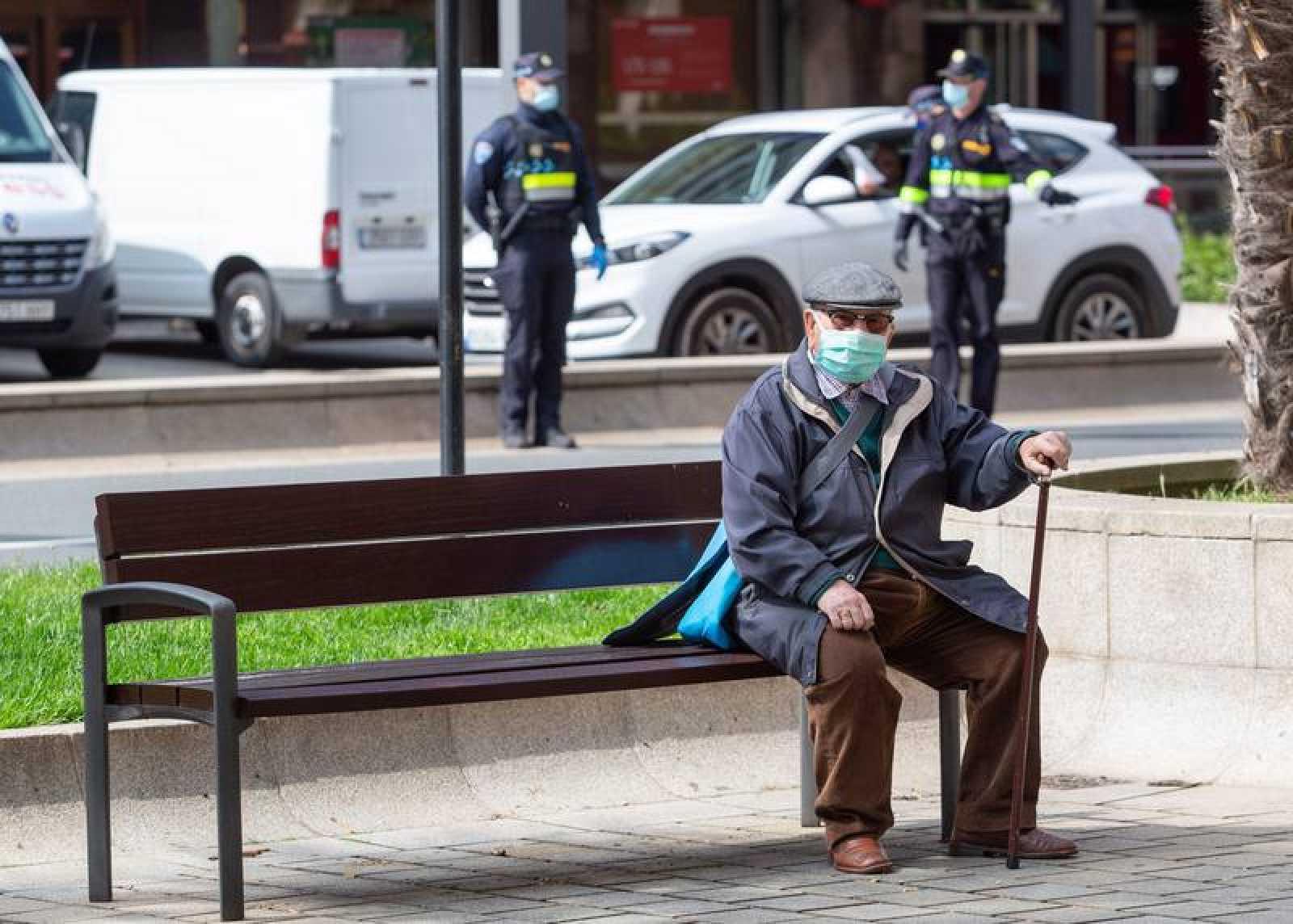Un hombre con mascarilla permanece sentado en un banco mientras a sus espaldas agentes de la Policía Nacional  trabajan
