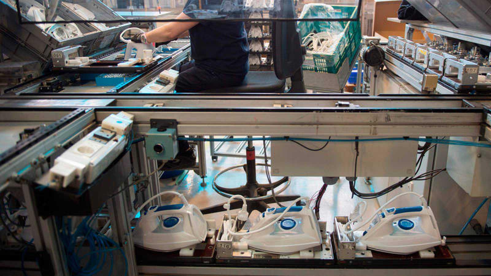 Una trabajadora ensambla planchas en una fábrica