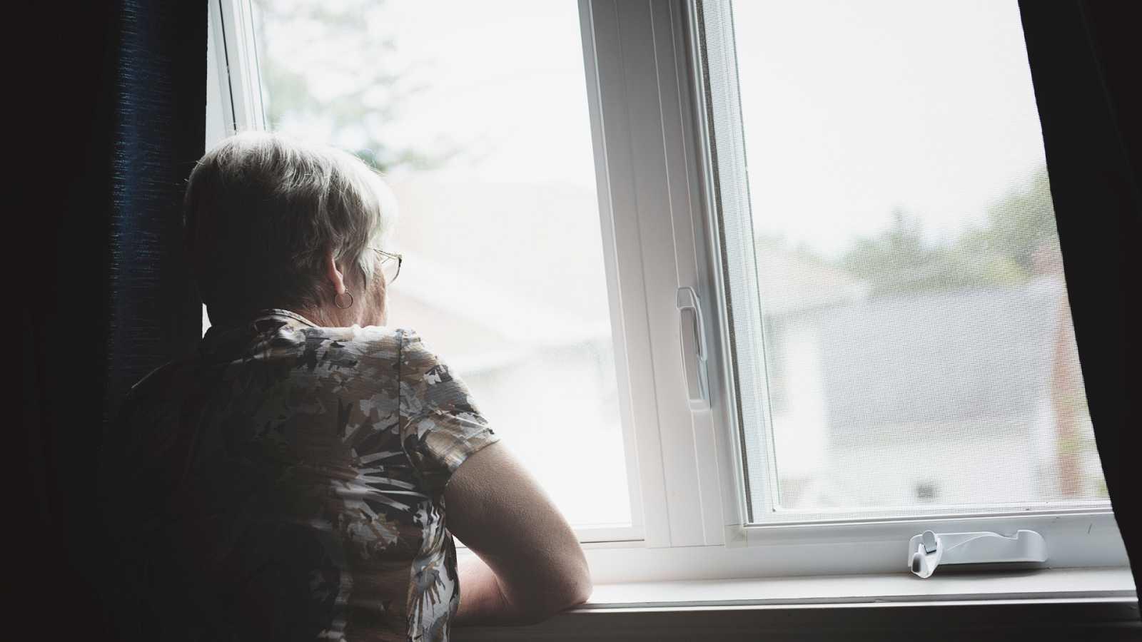 Una mujer se asoma por la ventana de su apartamento