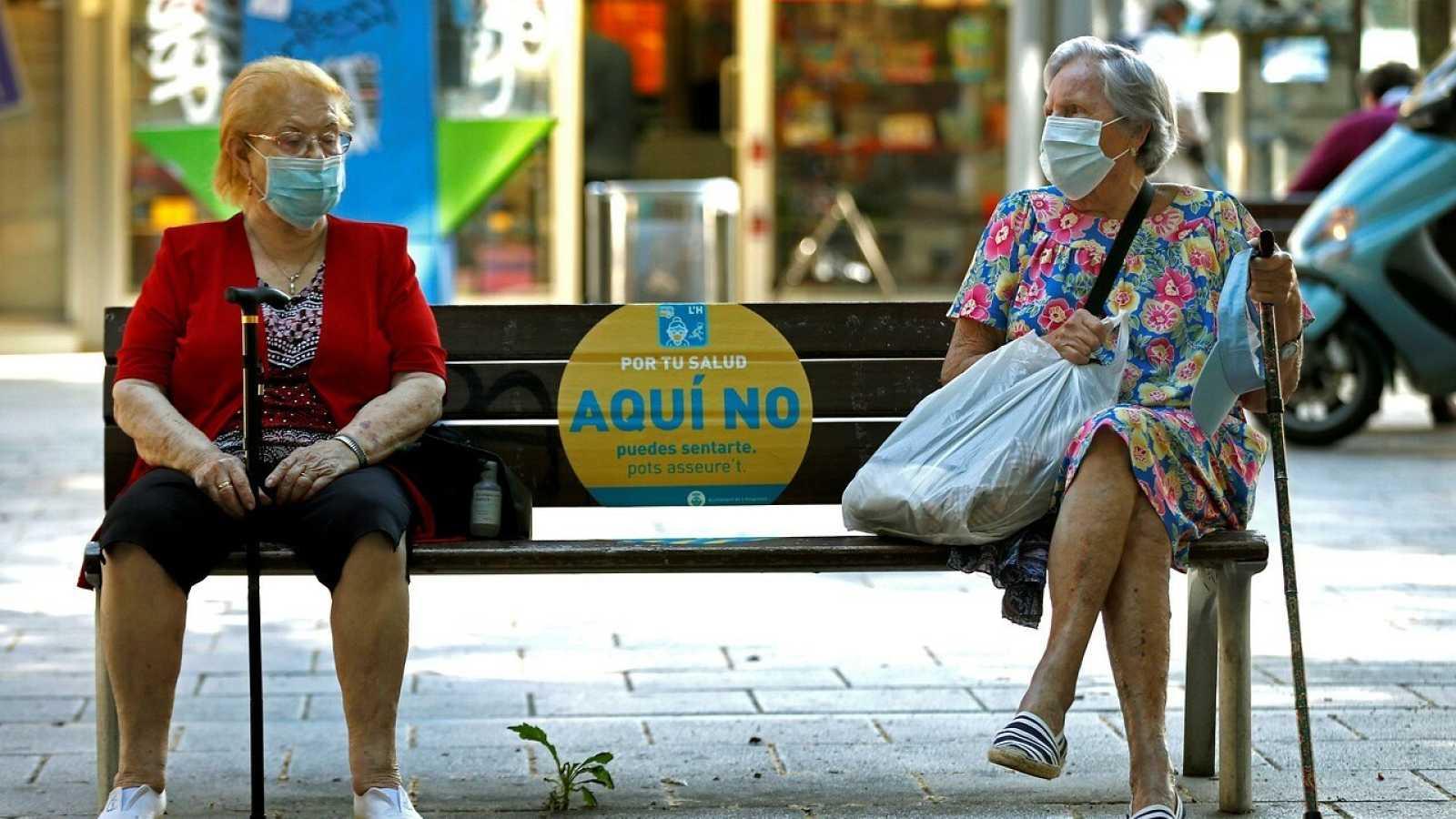 Dos mujeres conversan en un banco de L'Hospitalet (Barcelona) este jueves, cuando ha comenzado la obligatoriedad de llevar mascarilla en todos los espacios públicos. EFE/Toni Albir