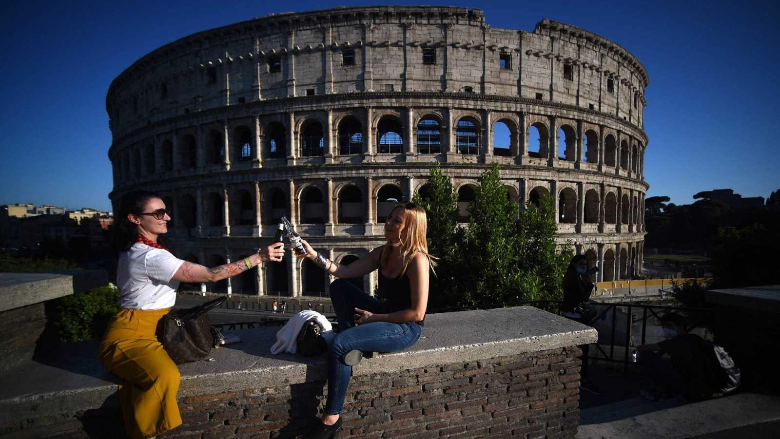 Dos mujeres brindan frente al Coliseo de Roma, tras relajarse las medidas de confinamiento por el coronavirus en Italia