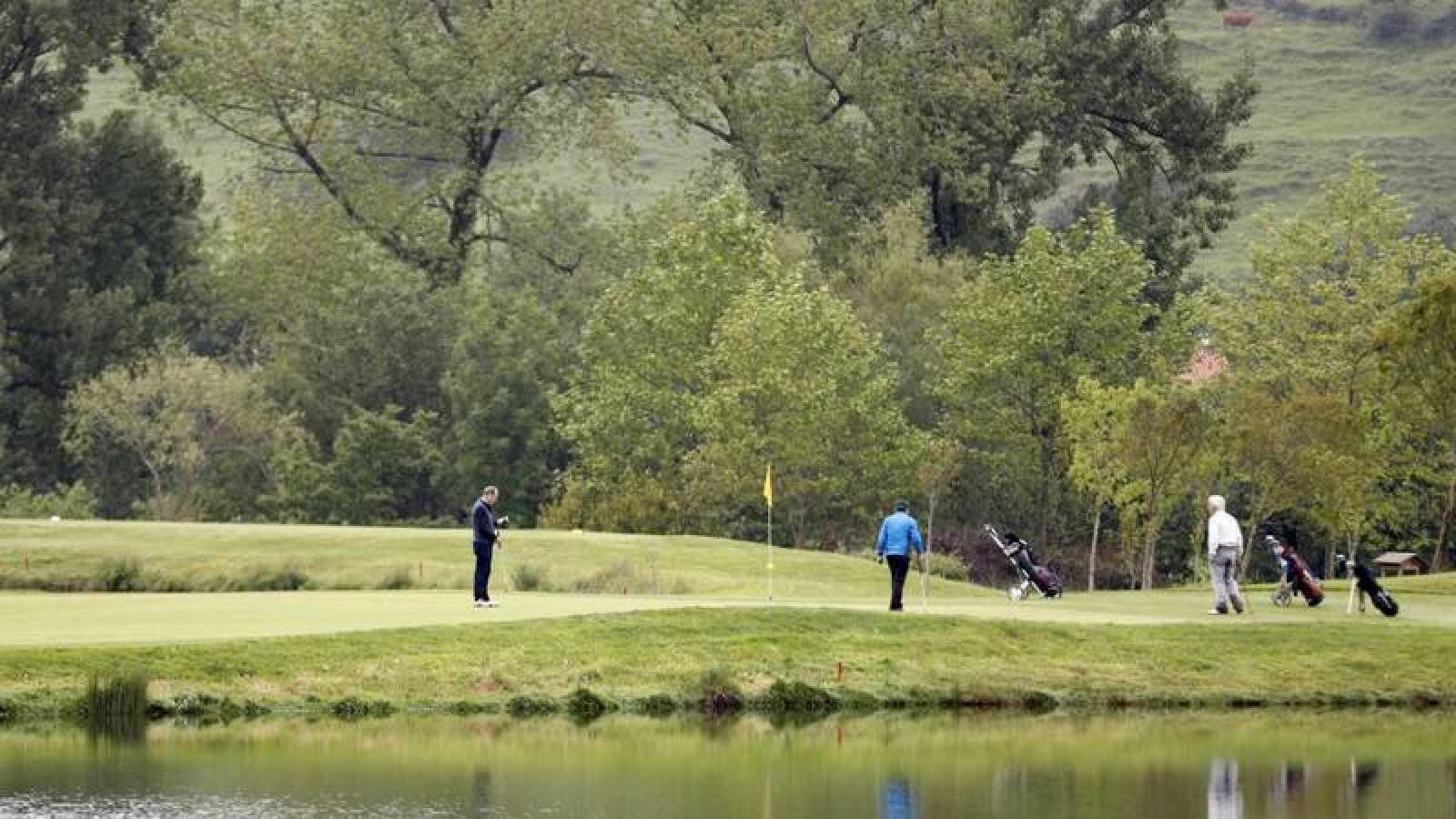 Tres jugadores mantienen la distancia social, en el campo público de golf de Meaztegi en Vizcaya.