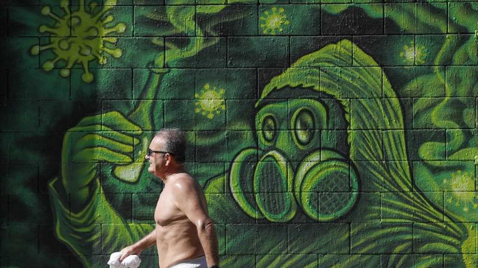 Un hombre camina ante un grafitti en una calle del centro de Barcelona este viernes