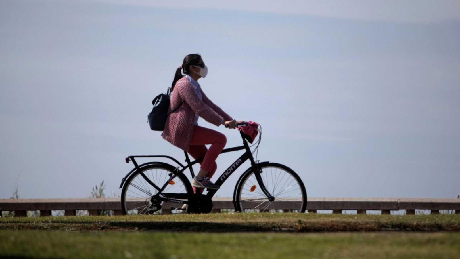 Una mujer con mascarilla circula en bicicleta por A Coruña