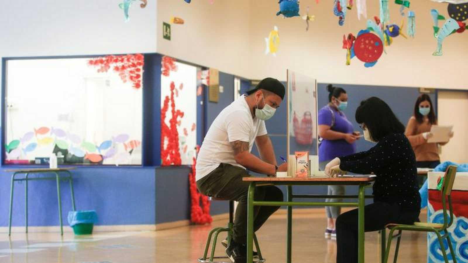 Una administrativa de la Escola l'Estel de Barcelona atiende a una persona.