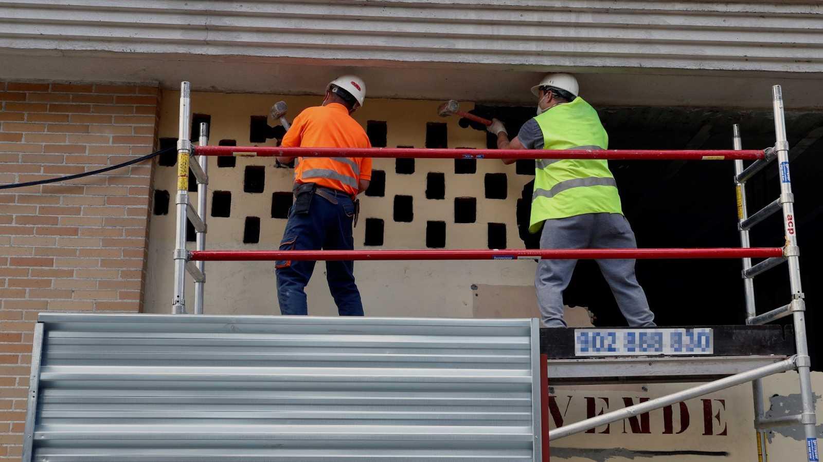 Dos operarios de la construcción realizan trabajos en la fachada de un edificio.