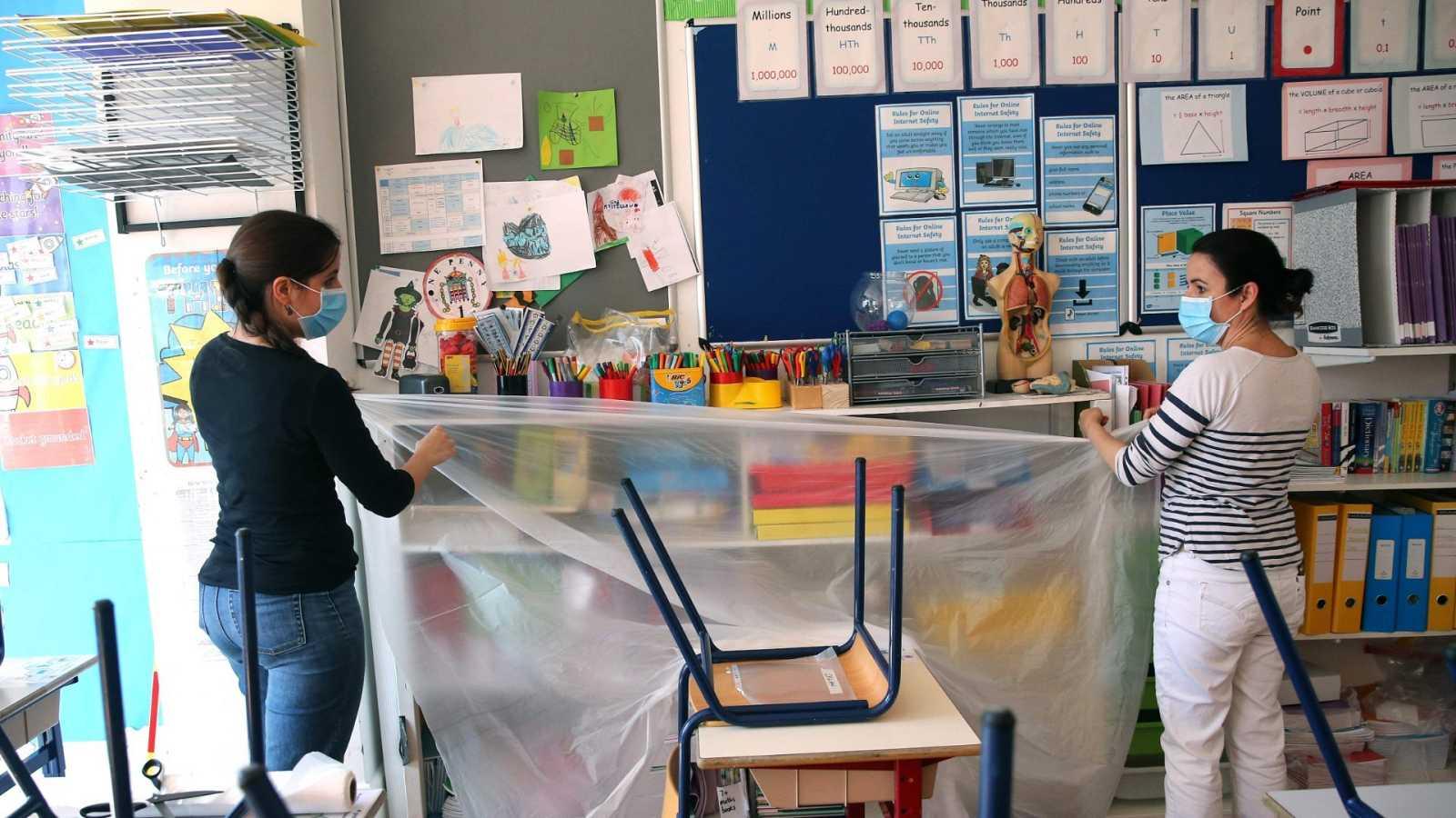 Dos profesoras cubren con plástico una estantería en un colegio de Londres.