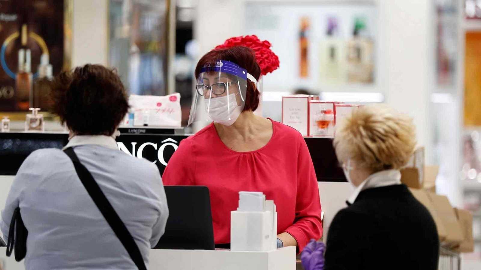 Una dependienta con mascarilla atiende a clientas que compran mascarillas en un supermercado