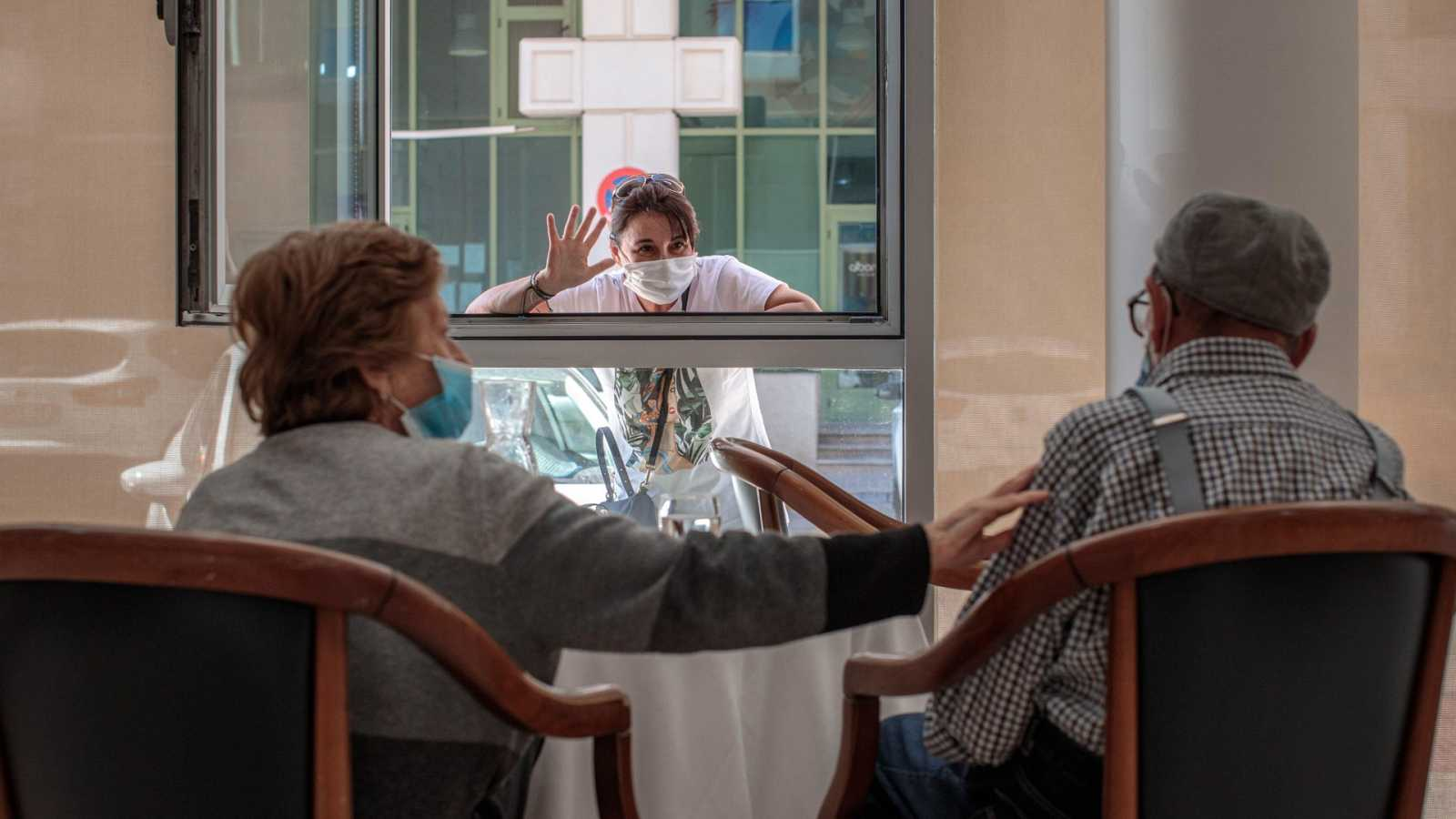Una mujer conversa con sus padres a través de una ventana habilitada en la residencia de mayores Ballesol Patacona, en Valencia, para que los residentes puedan recibir visitas de sus familiares.