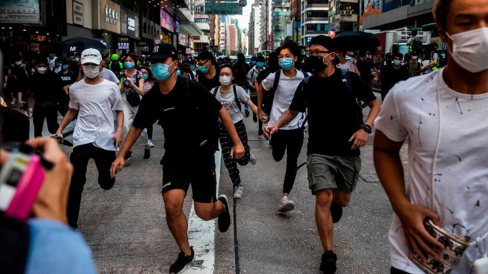 Manifestantes corren ante la llegada de la policía en Hong Kong
