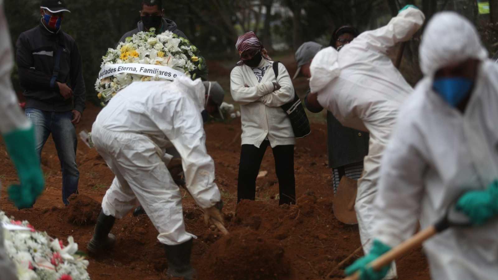 Una mujer asiste al entierro de su hijo, de 47 años, que murió con la enfermedad del coronavirus, la COVID-19, en Sao Paulo, Brasil.