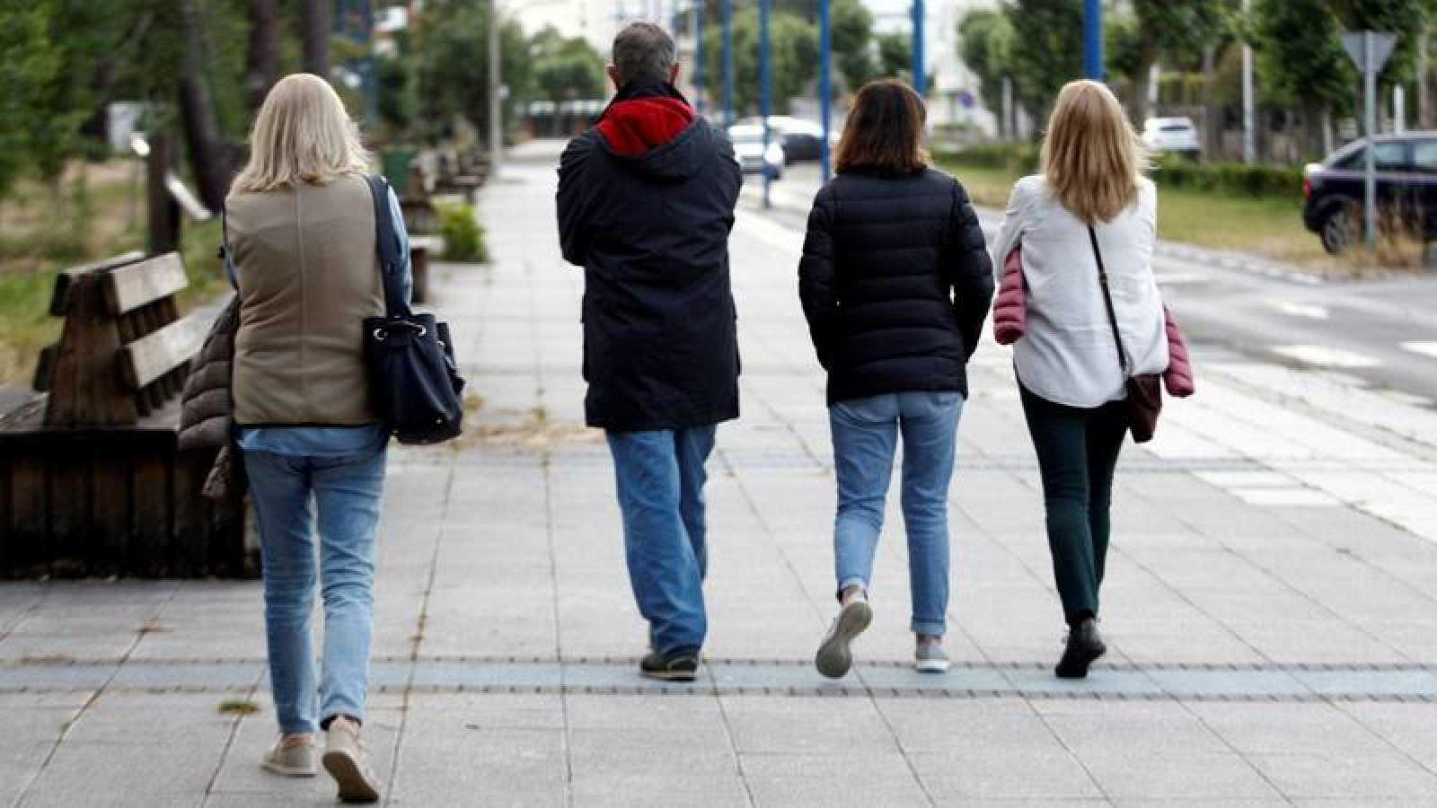 Varias personas dan un paseo en la tarde del jueves por la localidad coruñesa de Cabanas