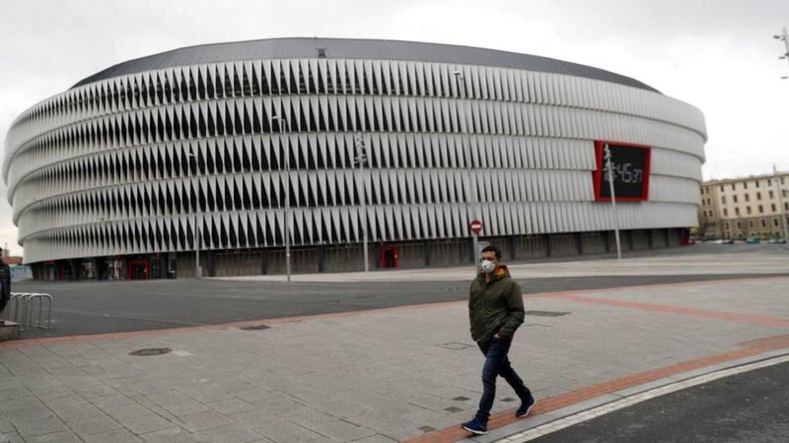 Un hombre con mascarilla pasa por delante del estadio de San Mamés