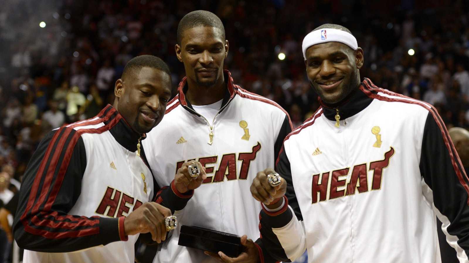 Wade (i), Bosh (c) y James (d) posan con el anillo de campeones de la NBA