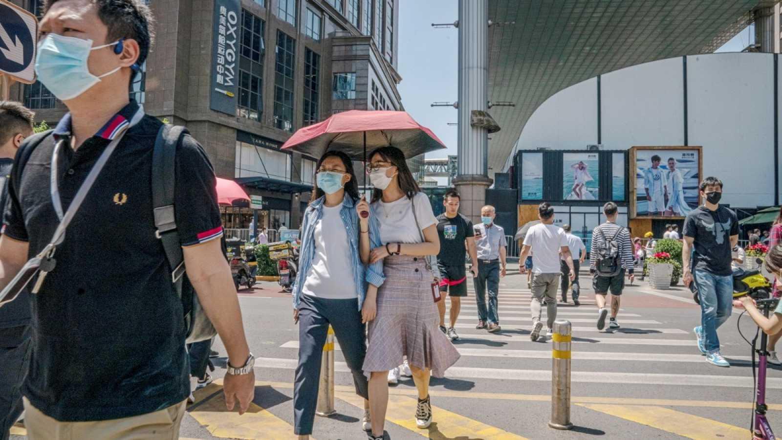 Viandantes con mascarilla cruzan la calle en el distrito comercial de Pekín, China, cuando el país ya ha conseguido controlar la pandemia de coronavirus.
