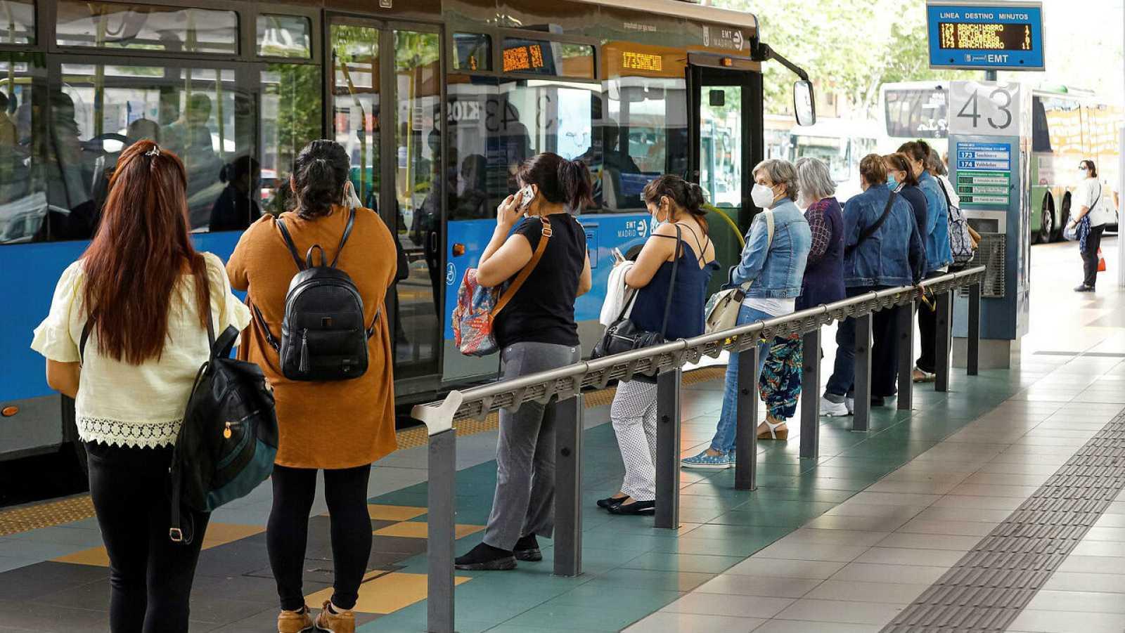Viajeros esperan la cola del autobús en Madrid mientras miran sus teléfonos móviles.