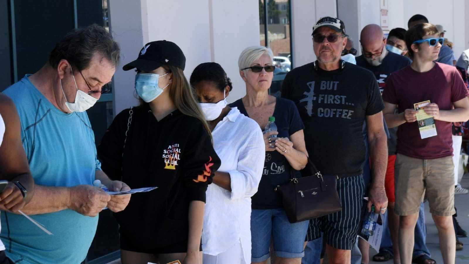 Un grupo de personas, algunas con mascarilla, se inscribe para votar en el estado de Nevada
