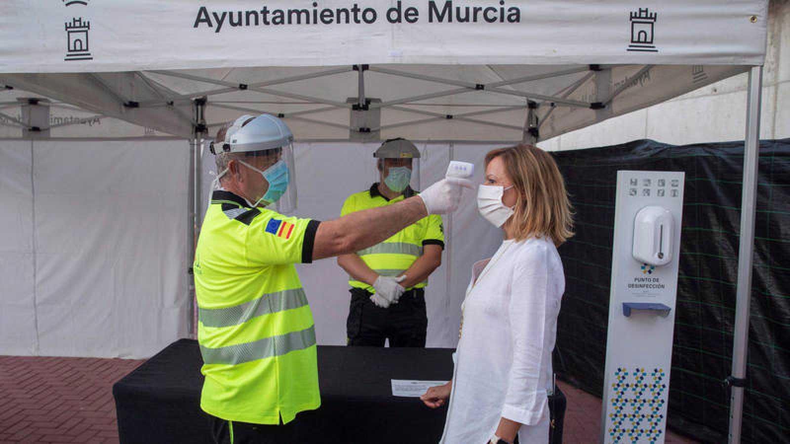 Un sanitario toma la temperatura a una mujer a la entrada al auditorio Murcia Parque