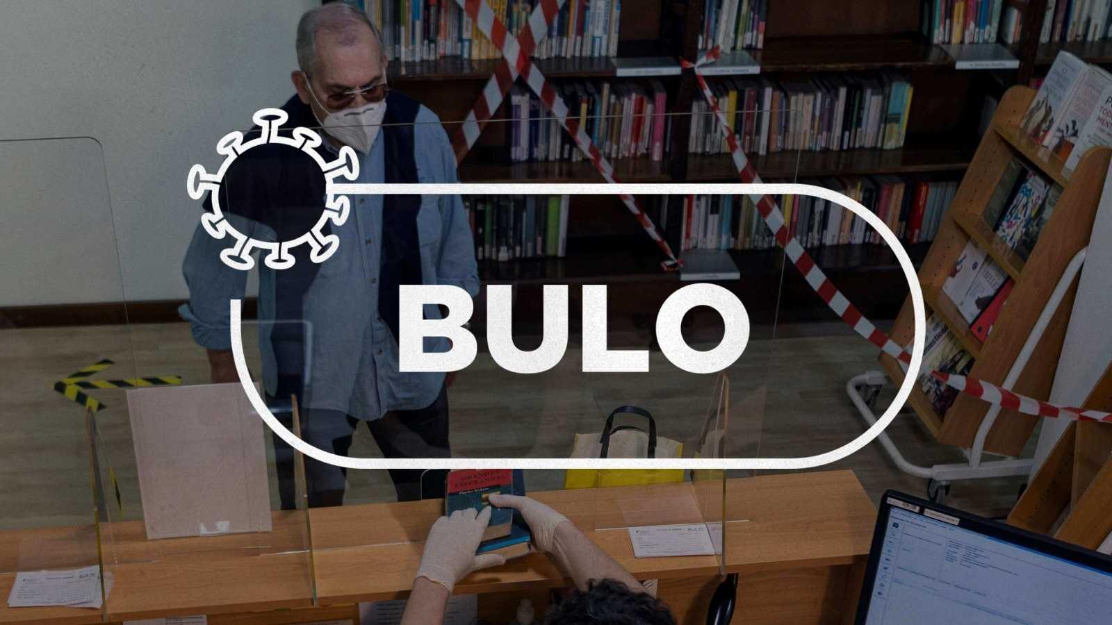 """Una persona con mascarilla hace gestiones en una oficina bajo el sello con la palabra """"bulo""""."""
