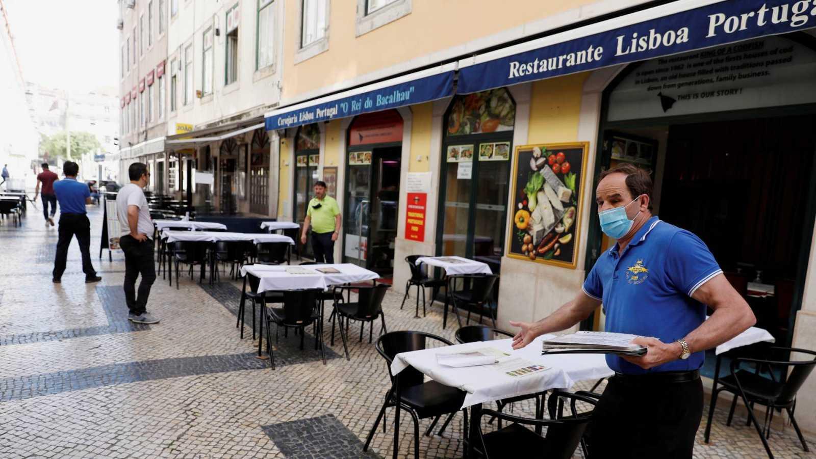 Un camarero invita a los transeúntes a sentarse en un restaurante del centro de Lisboa