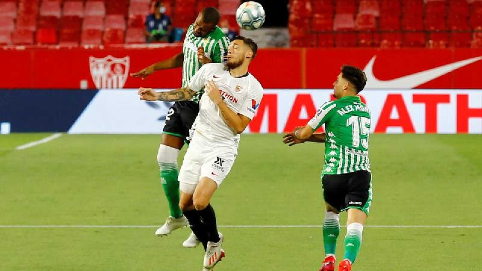 El sevillista Ocampos lucha un balón aéreo con el bético Sidnei.