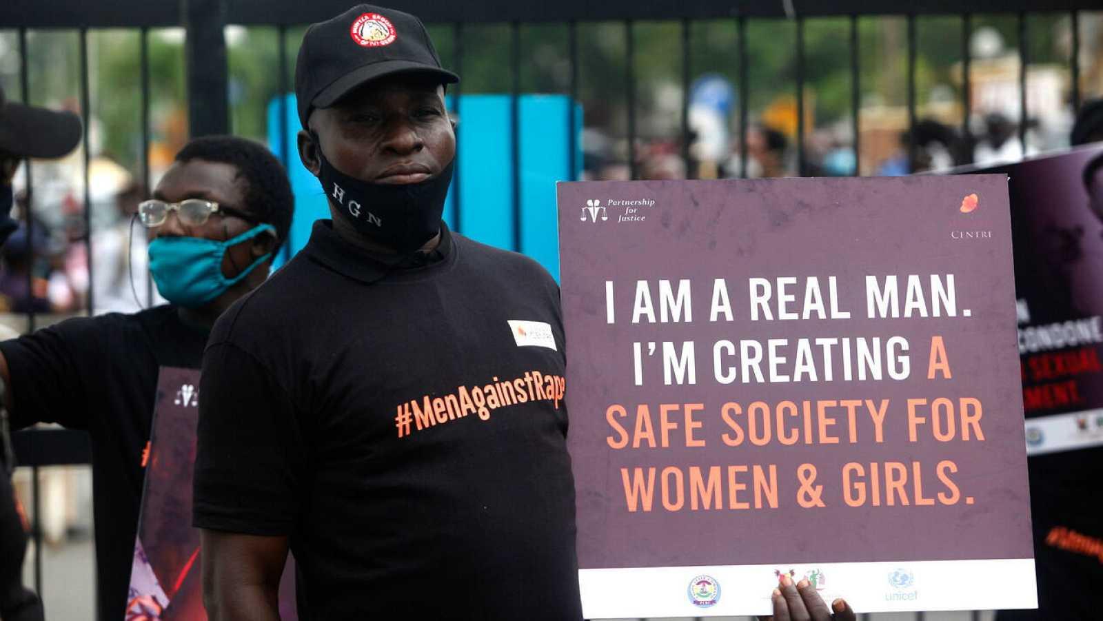 """Un miembro de la 'Coalición de Hombres contra la Violación' sostiene una pancarta en la que se puede leer """"soy un hombre de verdad. Estoy creando una sociedad segura para mujeres y niñas"""", durante una protesta callejera y una campaña de iluminación e"""