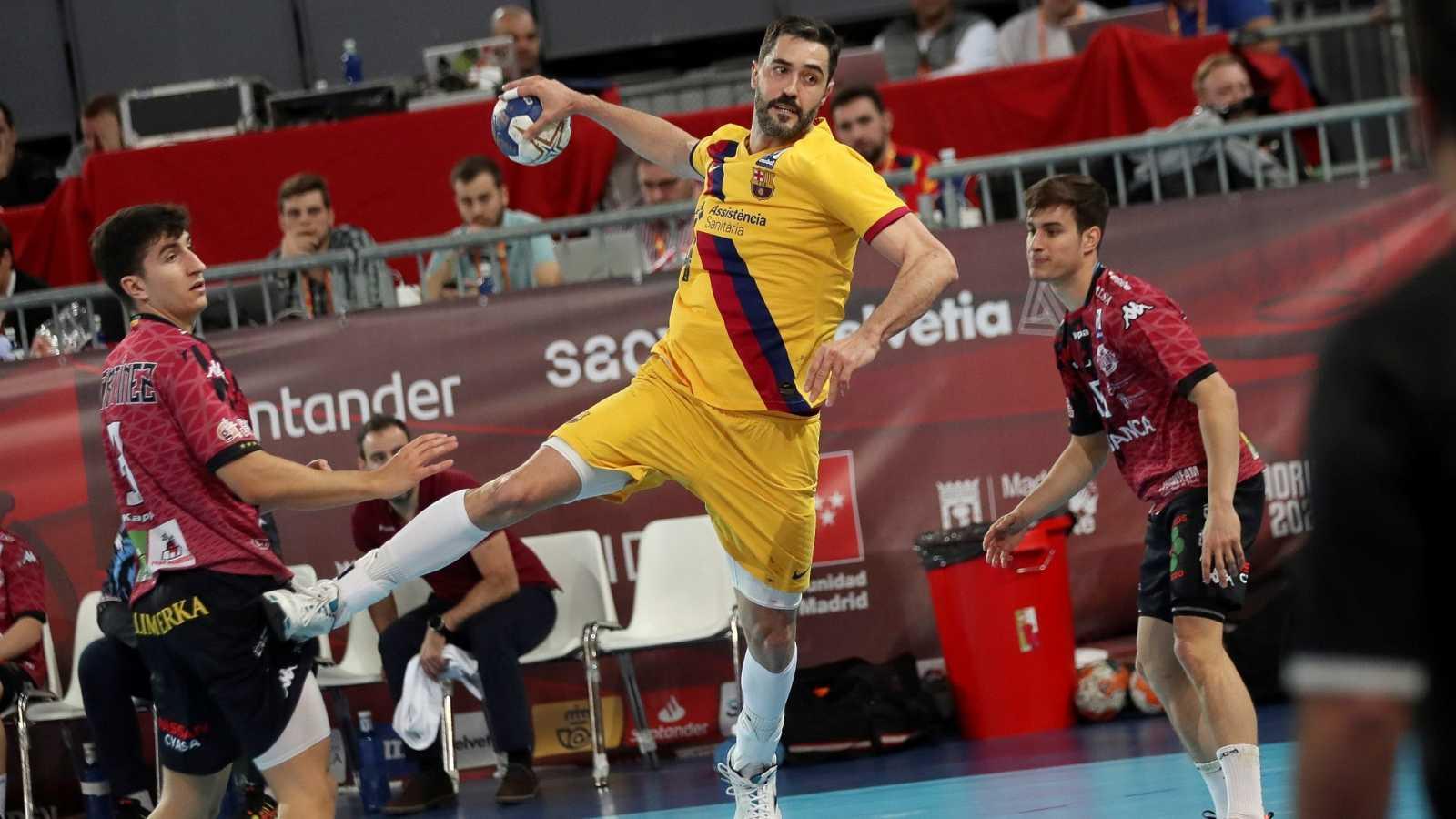 El jugador del FC Barcelona, Raúl Entrerrios (c), supera a los defensores de Ademar León durante el partido de semifinales de la Copa del Rey