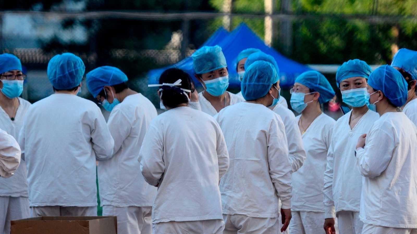 El personal médico se reúne en el Centro Deportivo Guang'an para realizar pruebas a las personas que visitaron o viven cerca del Mercado Xinfadi en Pekín