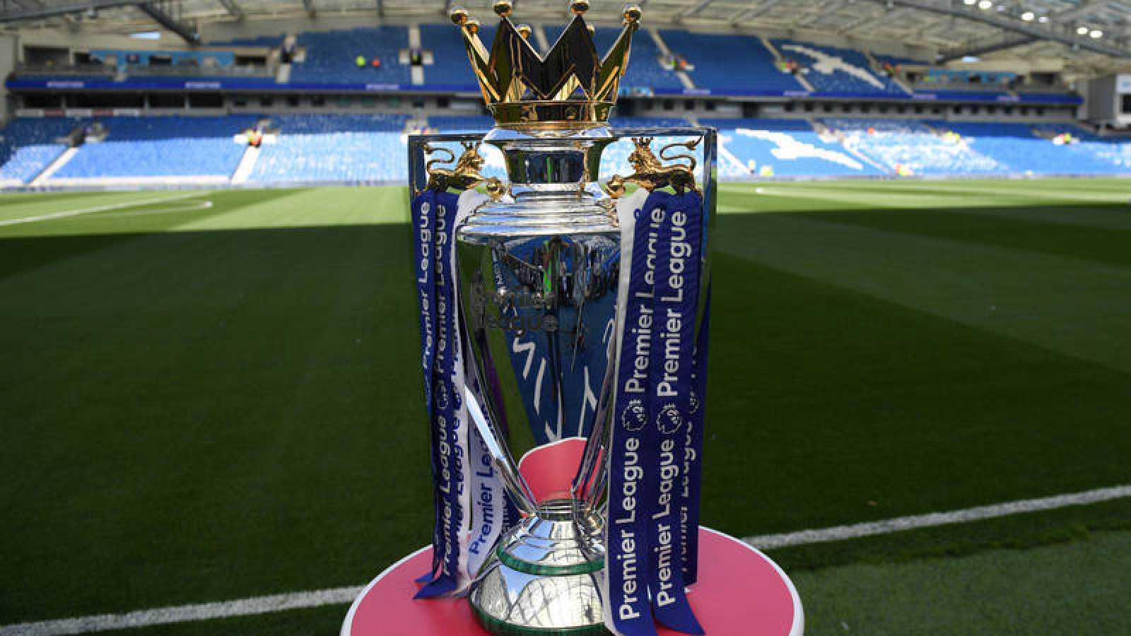 El trofeo de la Premier League sobre una peana en un campo