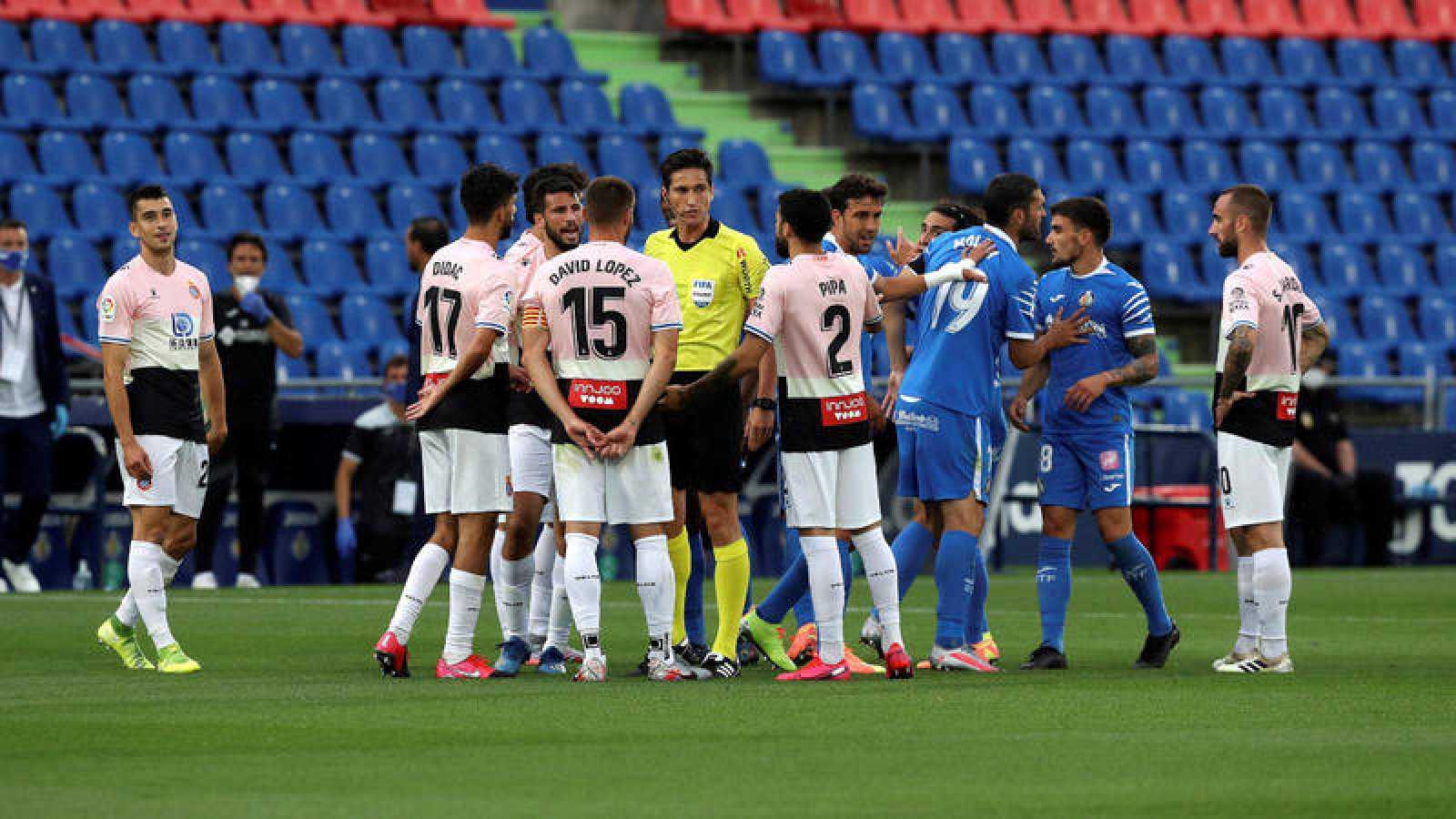 Jugadores del Getafe y el Espanyol rodean al árbitro