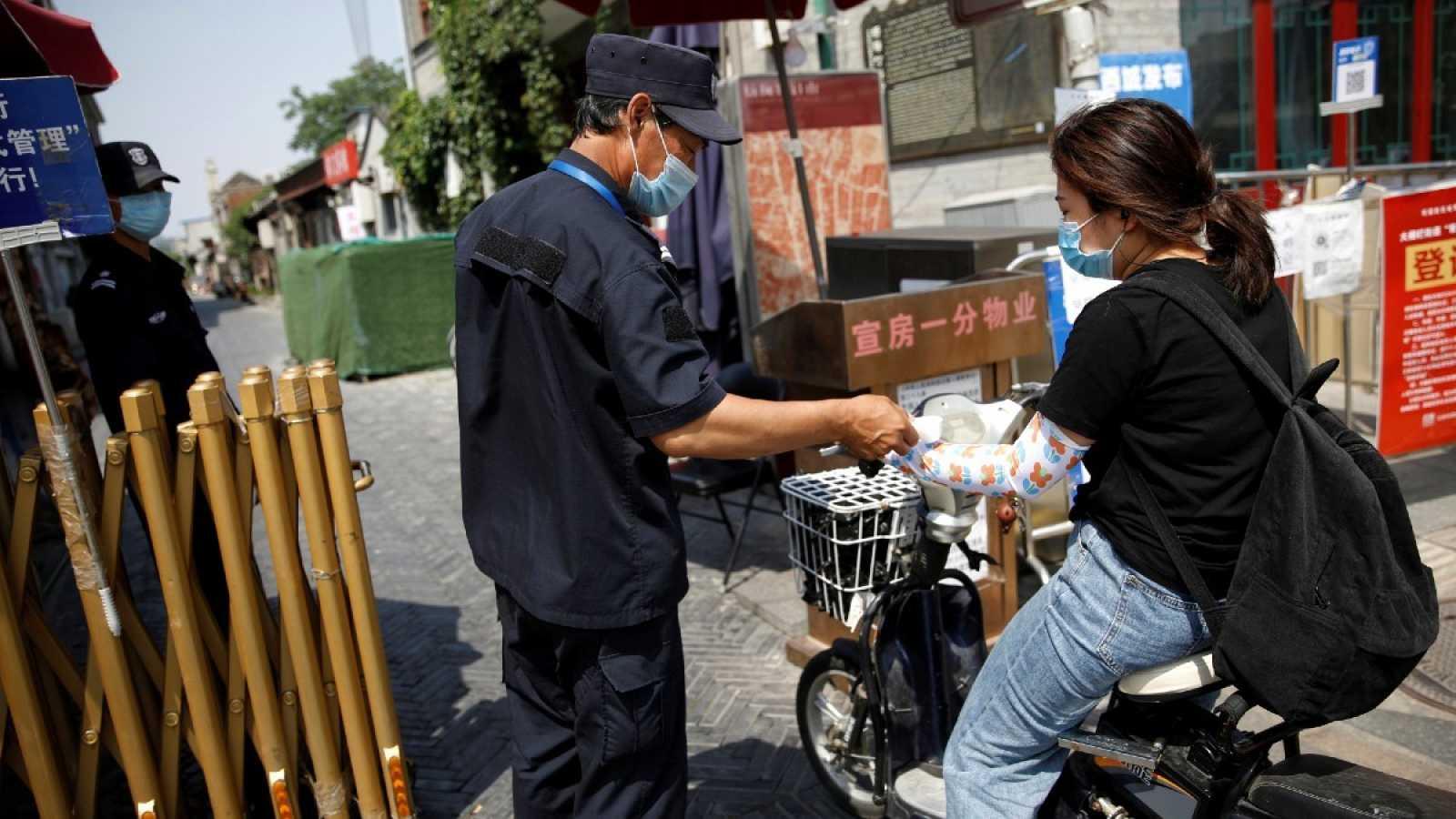 Un guardia de seguridad con mascarilla toma la temperatura de una mujer en una bicicleta en Pekín